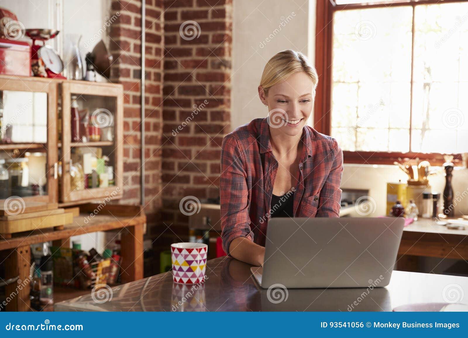 Junge Frau, die Computer in der Küche, ehrliche Ansicht des Abschlusses verwendet