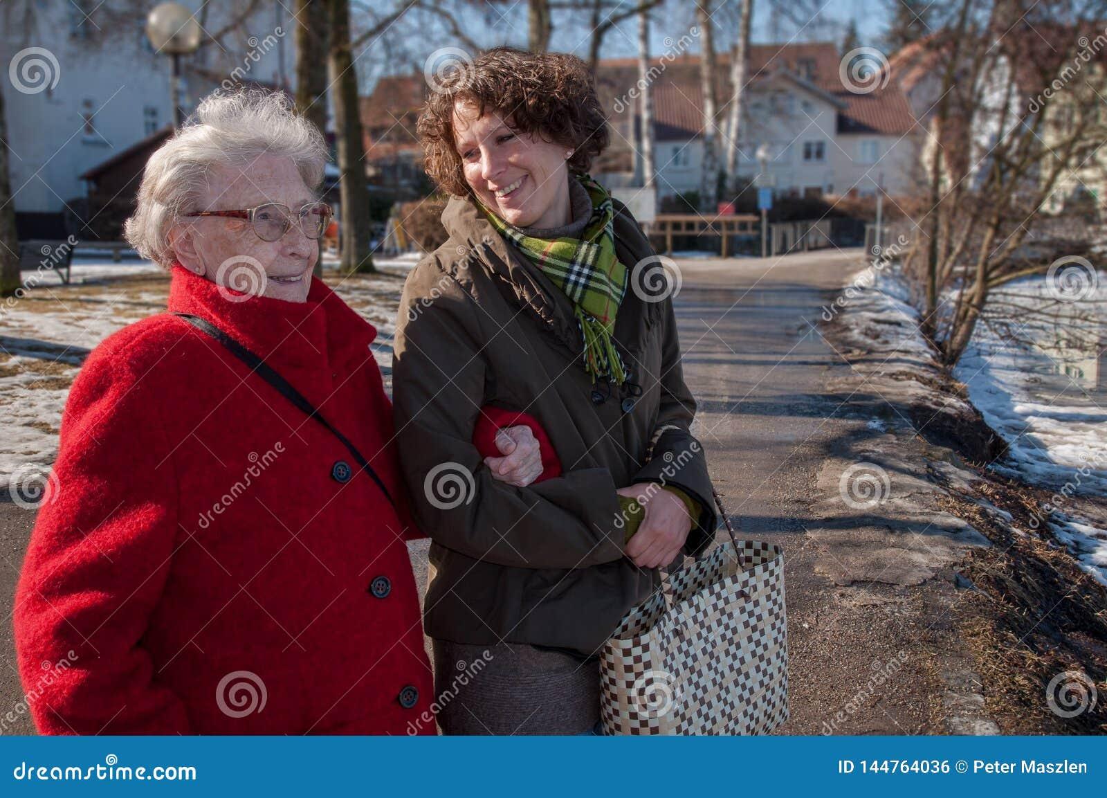 Junge Frau, die den Einkauf mit älterer Frau anstrebt