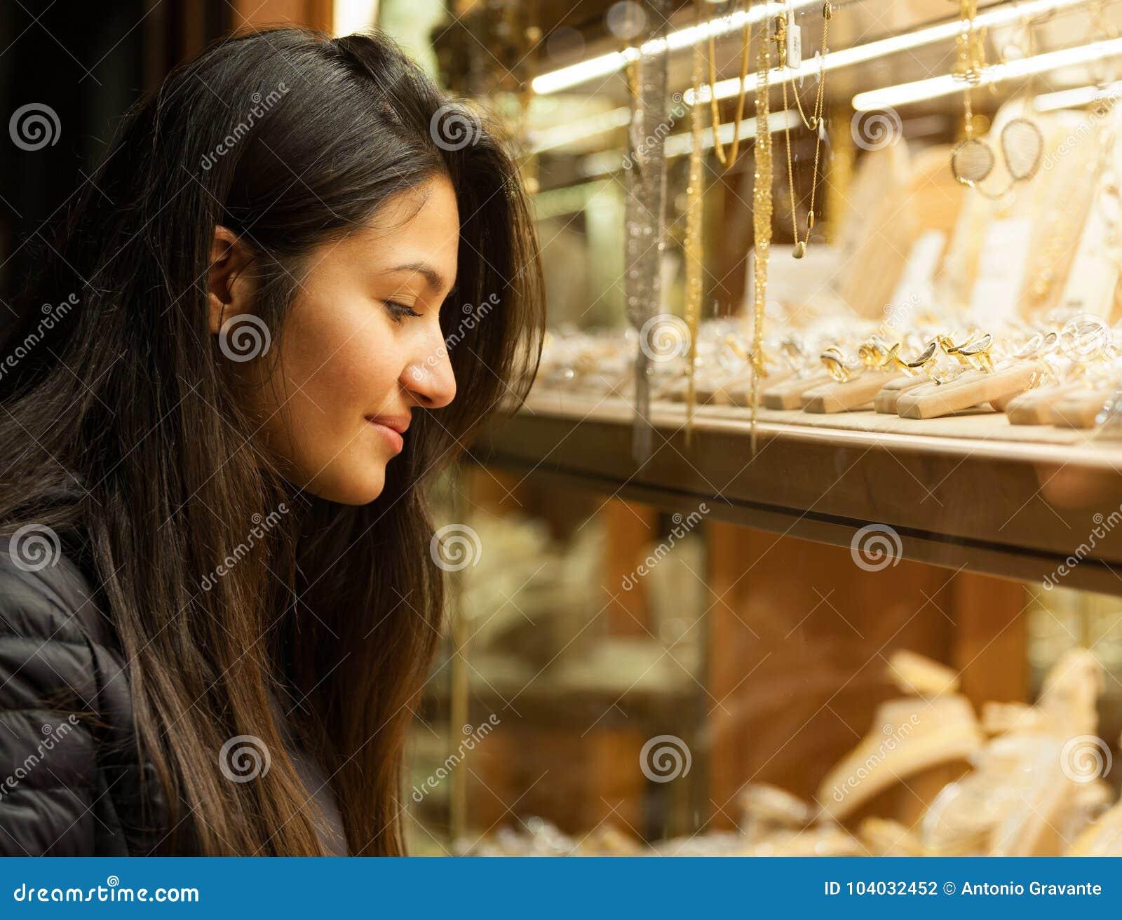 Junge Frau, die den Schaukasten eines Schmucks im Freien betrachtet