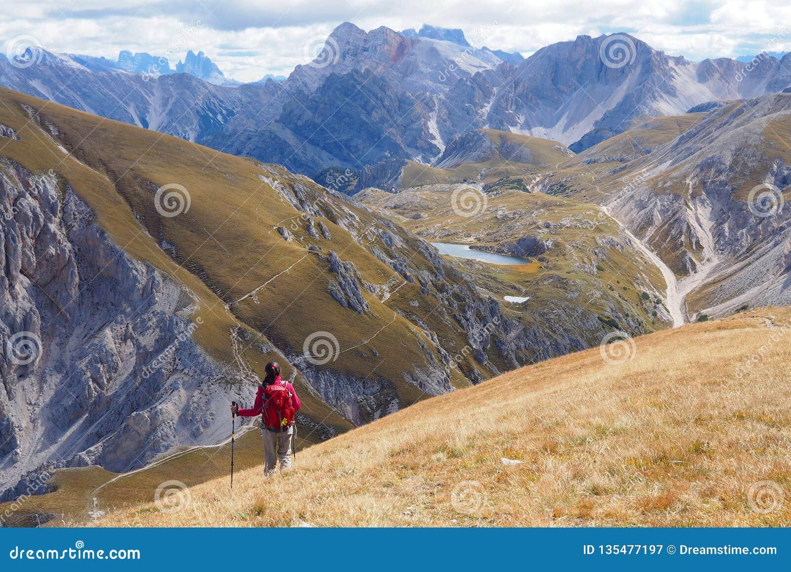 Junge Frau, die in der breiten Berglandschaft wandert