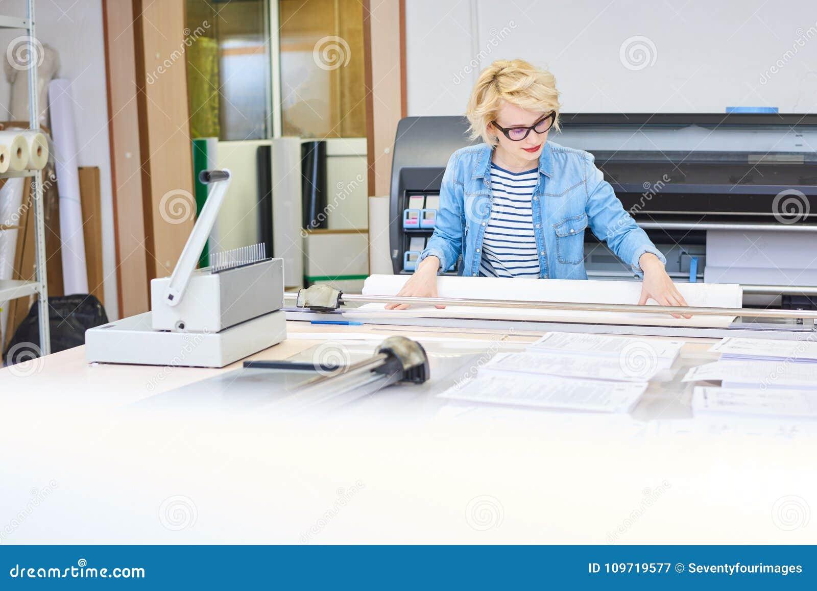 Junge Frau, die in der Druckerei arbeitet