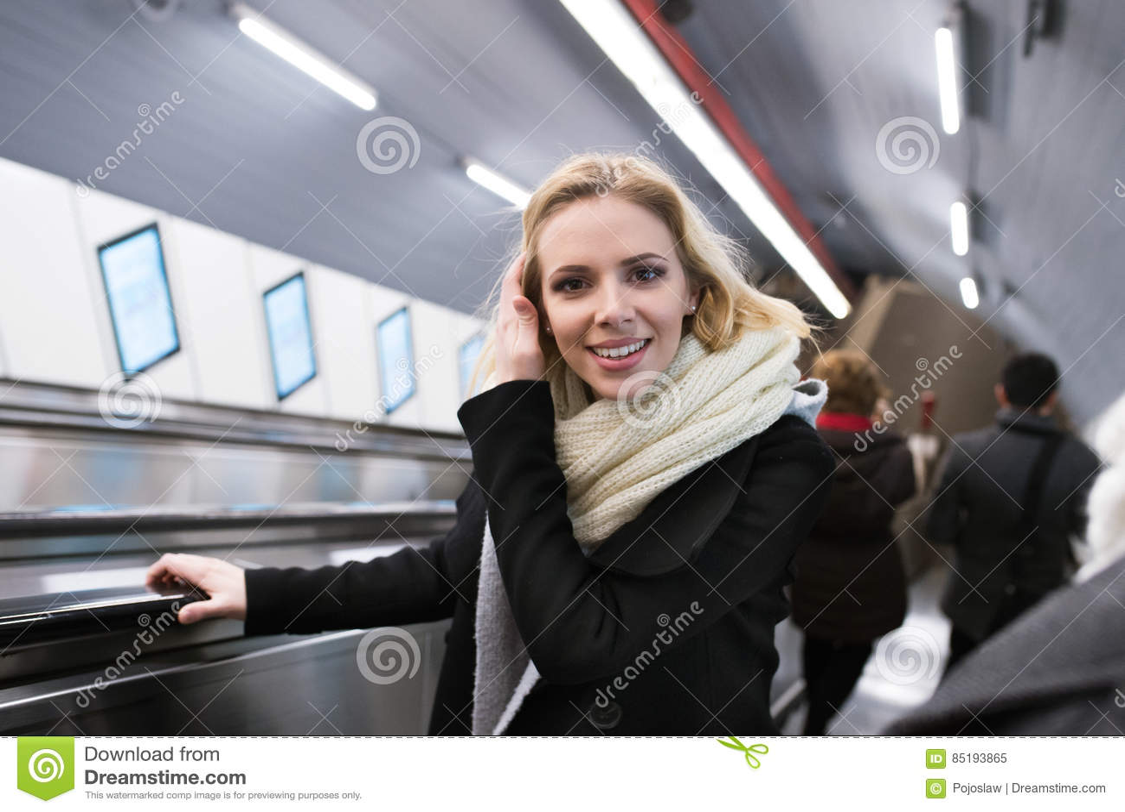 junge frau, die an der rolltreppe in wien-u-bahn steht