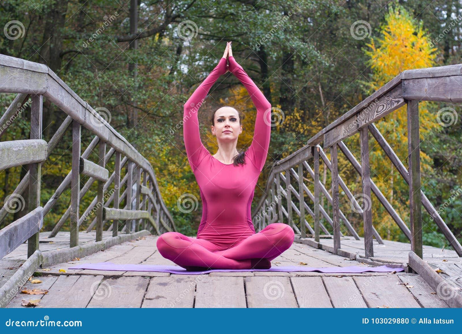 Junge Frau, die in der Yogalage auf Holzbrücke im Herbst steht