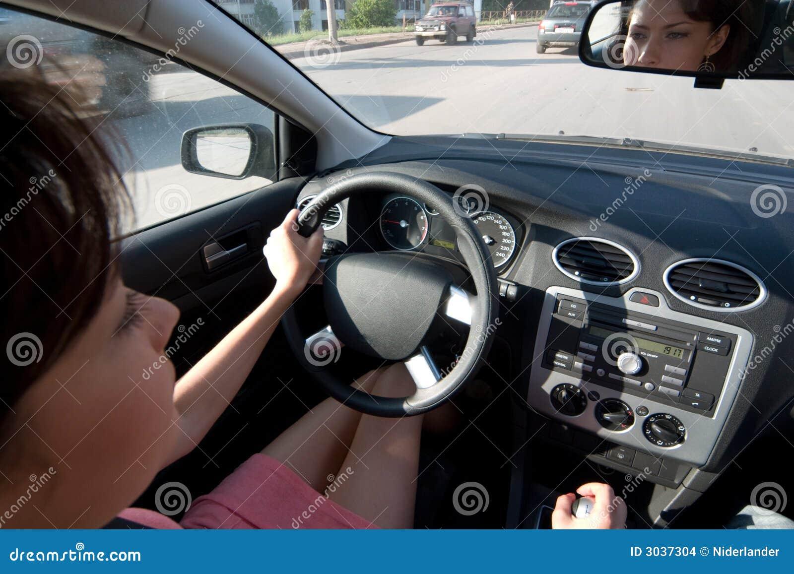 Junge Frau, die ein Auto antreibt