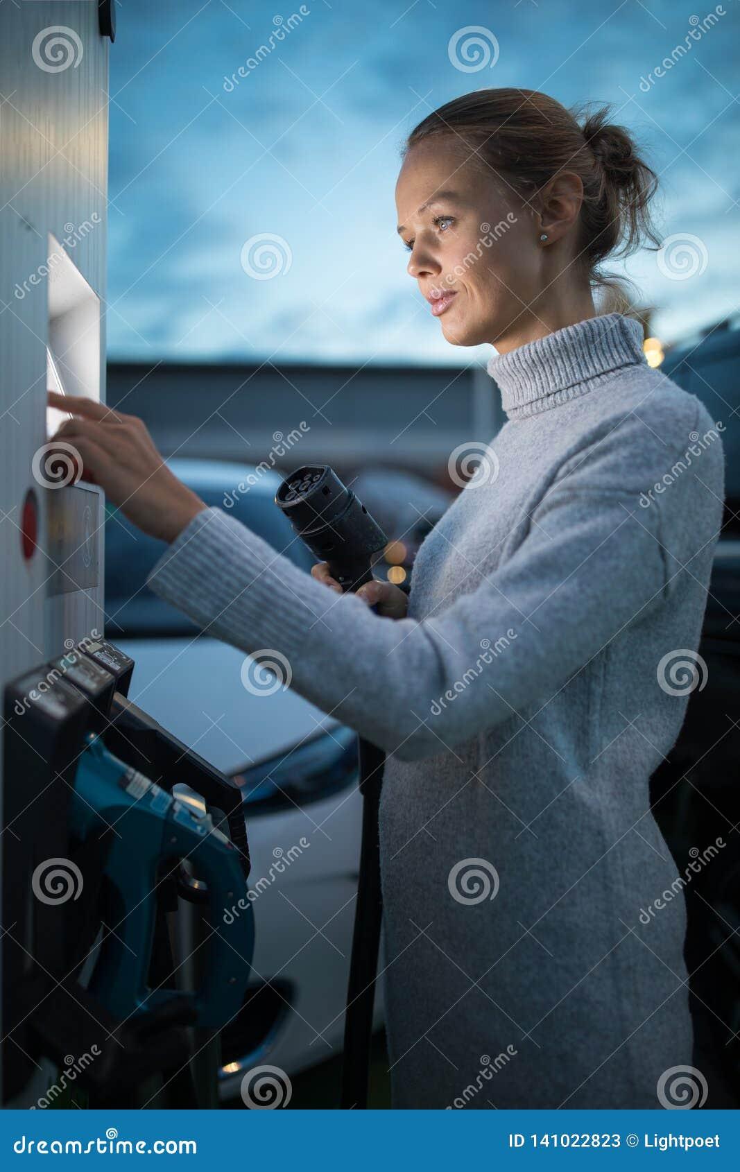 Junge Frau, die ein Elektro-Mobil auflädt