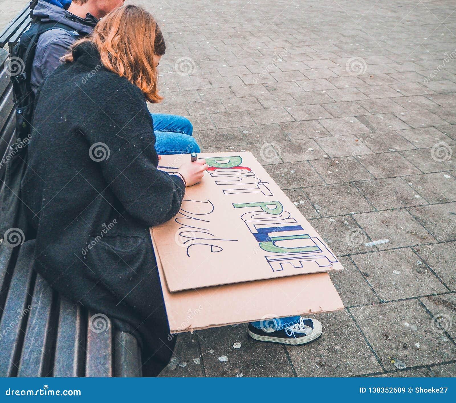 Junge Frau, die ein handgemachtes Plakat als Anruf für Aktion während eines Demonstrationszugs gegen Klimawandel macht