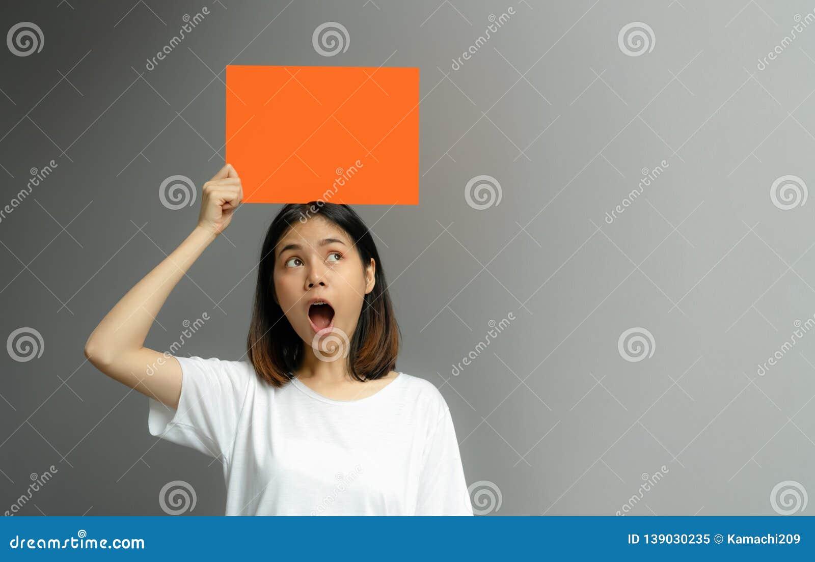 Junge Frau, die ein leeres Plakat für Text auf einem weißen Hintergrund hält