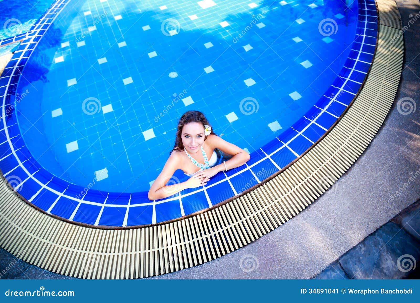 Junge Frau, die in einem Swimmingpool steht