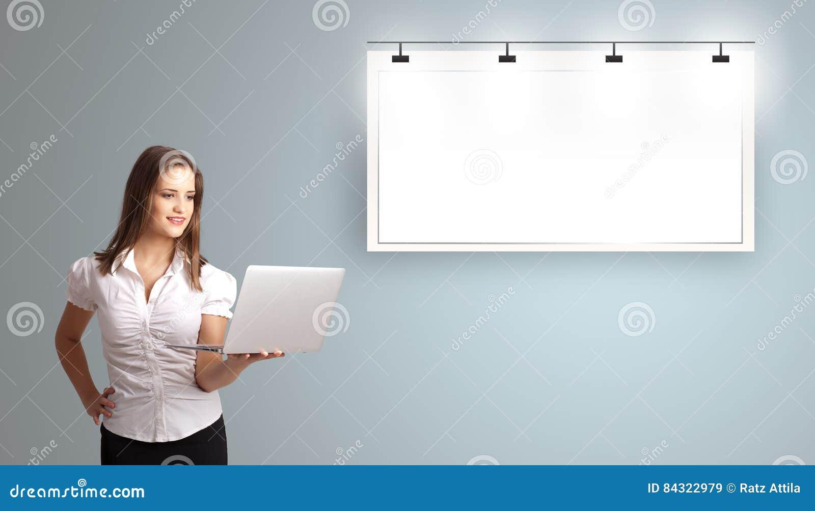 Junge Frau, die einen Laptop hält und modernen Kopienraum darstellt