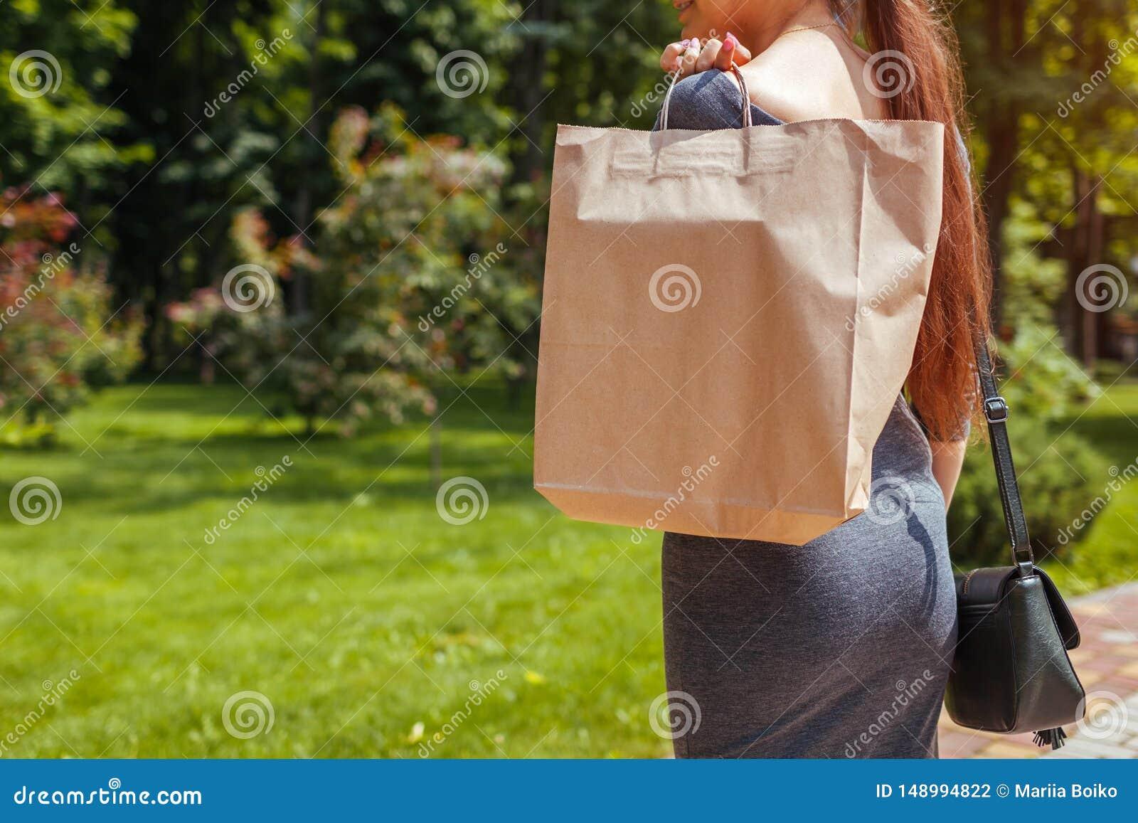 Junge Frau, die Einkaufspapiert?ten im Sommerpark h?lt und modische Ausstattung tr?gt