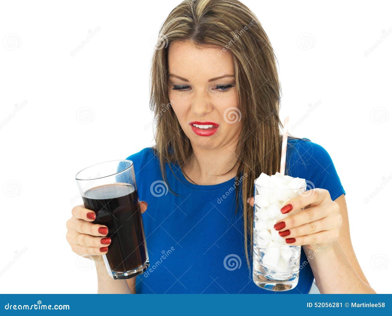 Junge Frau, die hohen Sugar Fizzy Drink trinkt