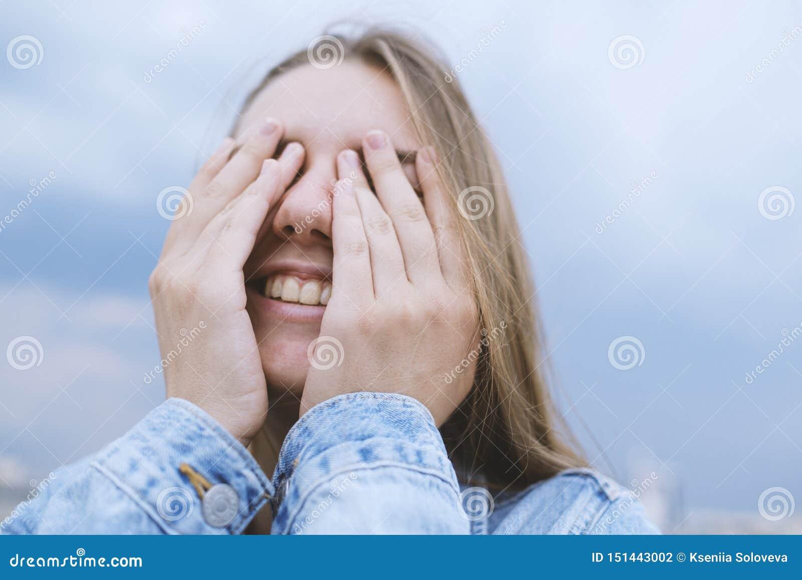 Junge Frau, die ihre Augen mit ihren H?nden abdeckt Positive Gefühle, Gelächter, Lächeln, Freude