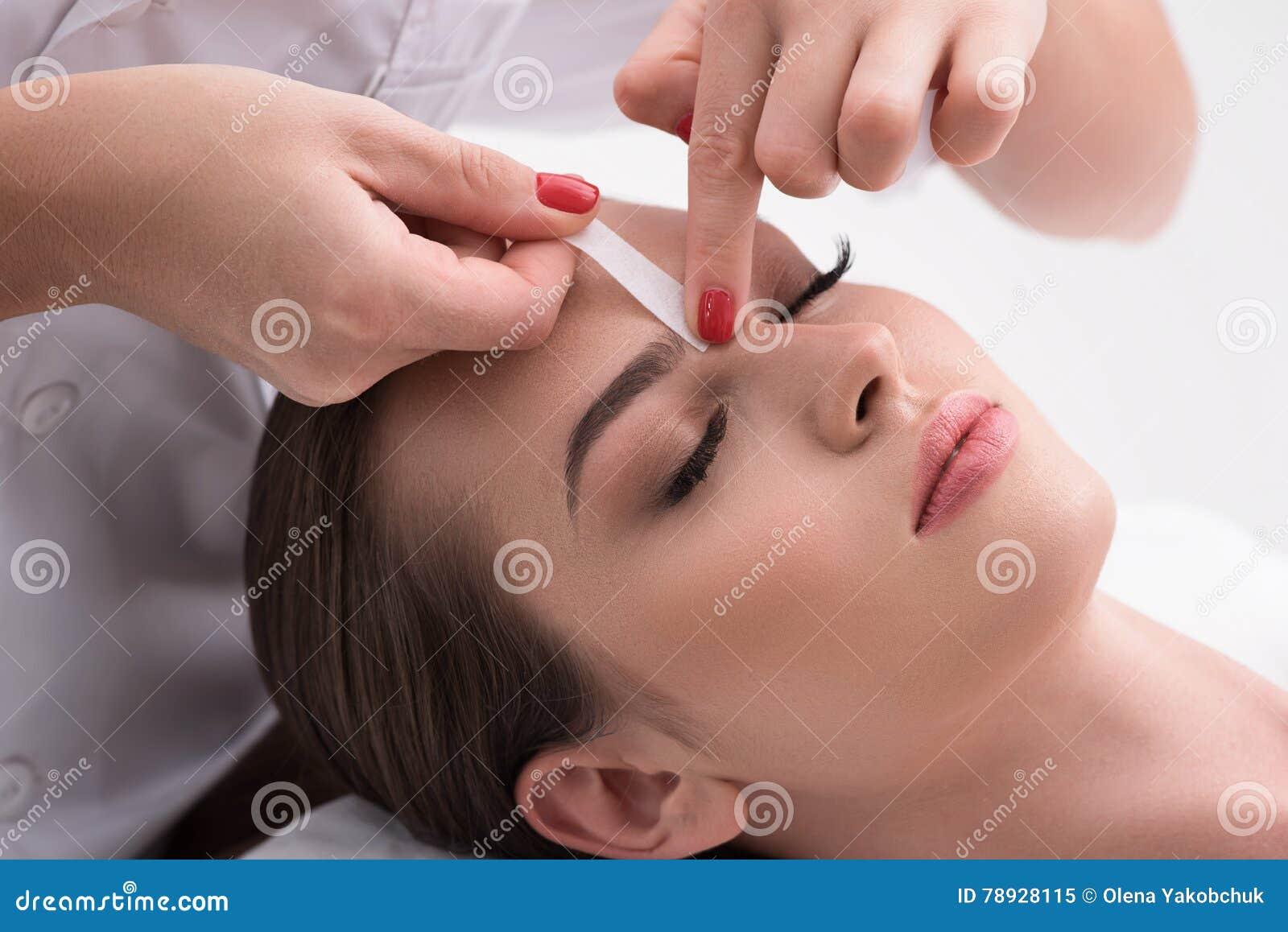 Junge Frau, die ihre Augenbrauen im Schönheitssaal auszupft
