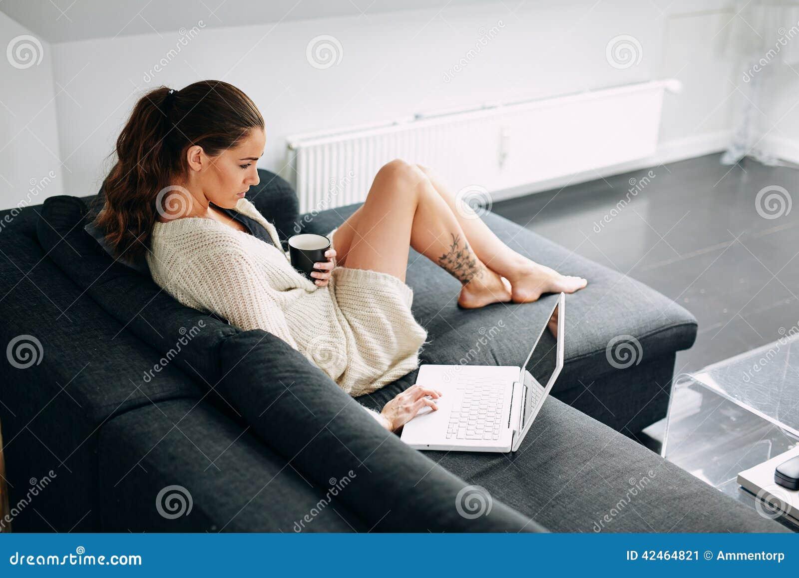 Junge Frau, die ihre E-Mail am Morgen überprüft