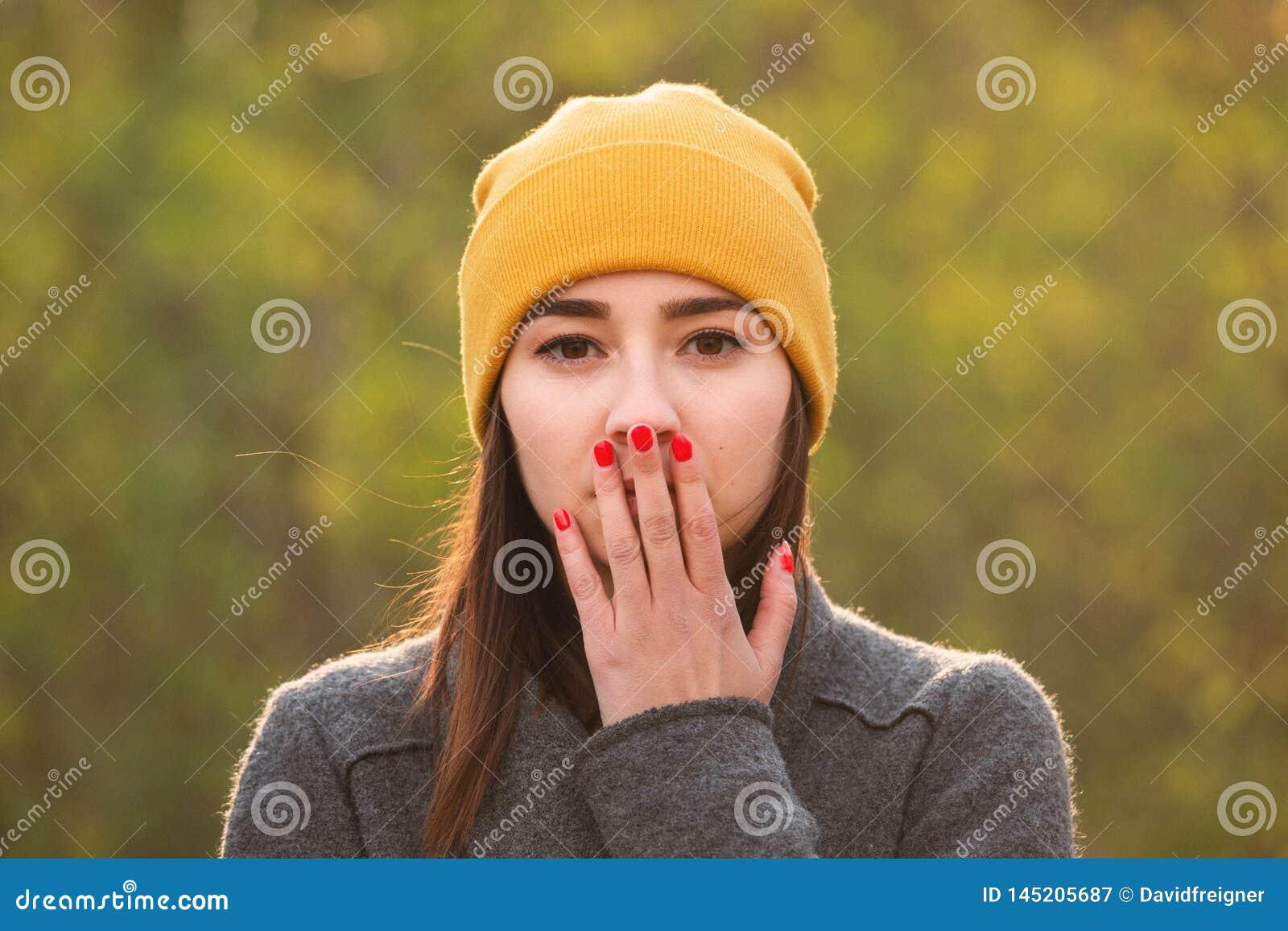Junge Frau, die ihren Mund mit ihrer Hand bedeckt