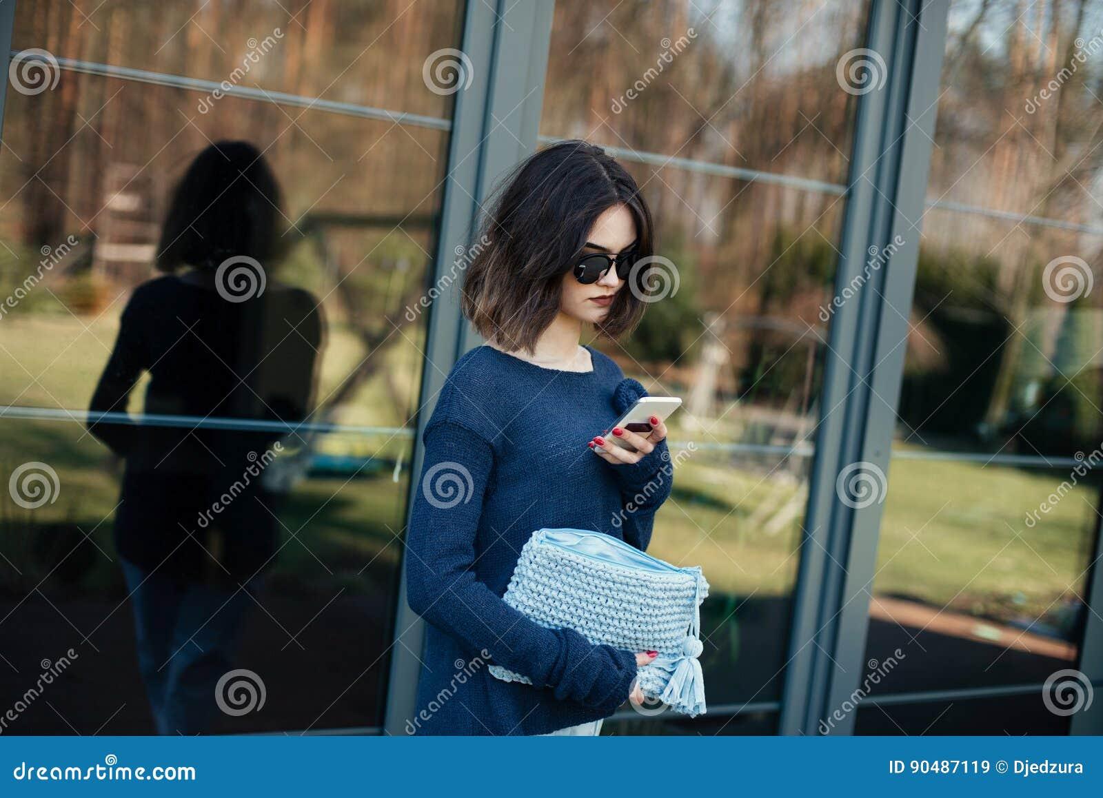 Junge Frau, die ihren Smartphone auf Terrasse verwendet