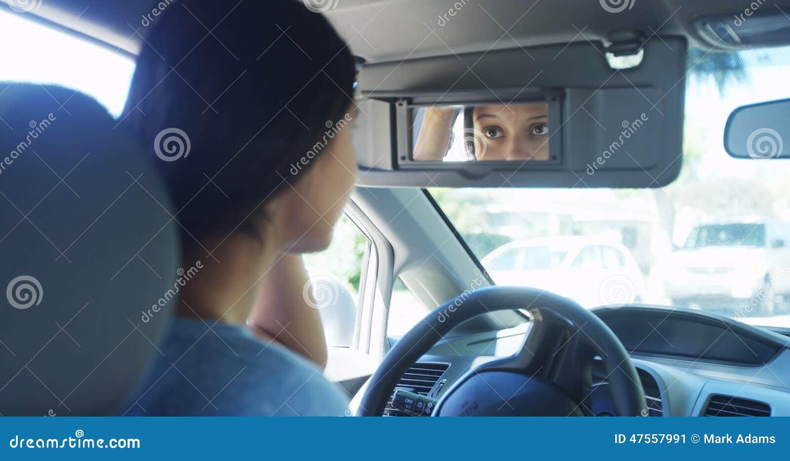 Spiegel Make Up : Junge frau die im auto überprüft ihr make up im spiegel sitzt
