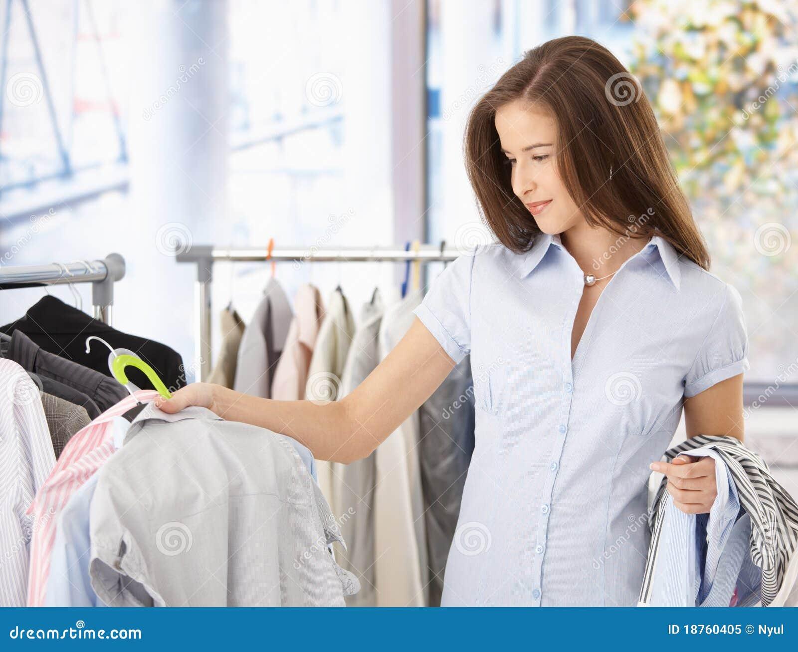 Junge Frau, die im Kleidungspeicher schaut