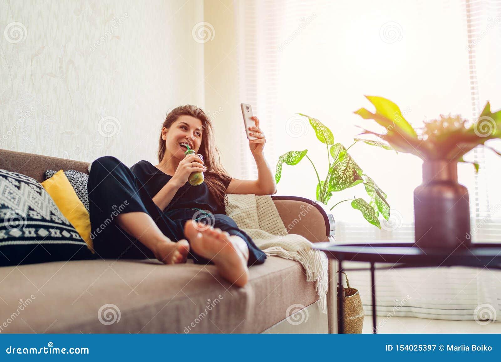 Junge Frau, die im Wohnzimmer und in trinkendem Smoothie unter Verwendung des Smartphone sich entspannt Gesunde Di?t