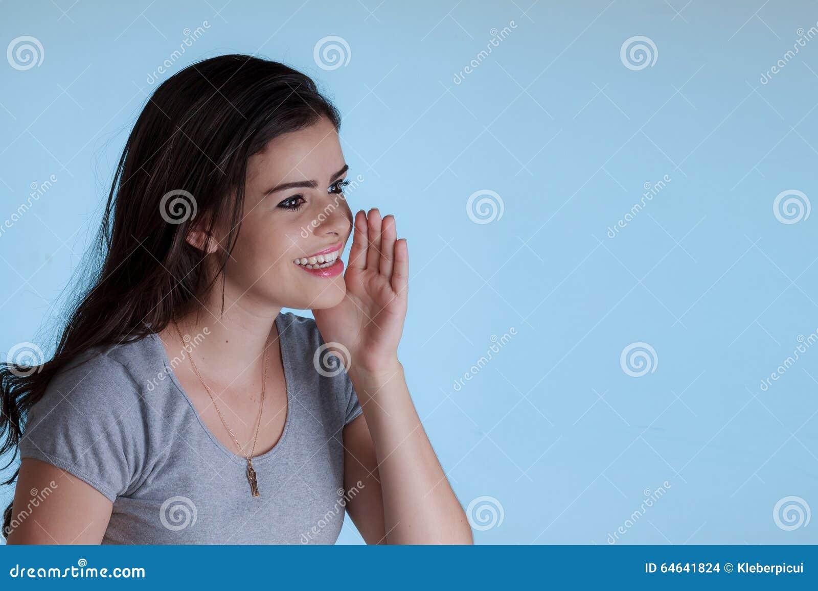 Junge Frau, Die Jemand Mit Einer Hand Nahe Bei Dem Mund