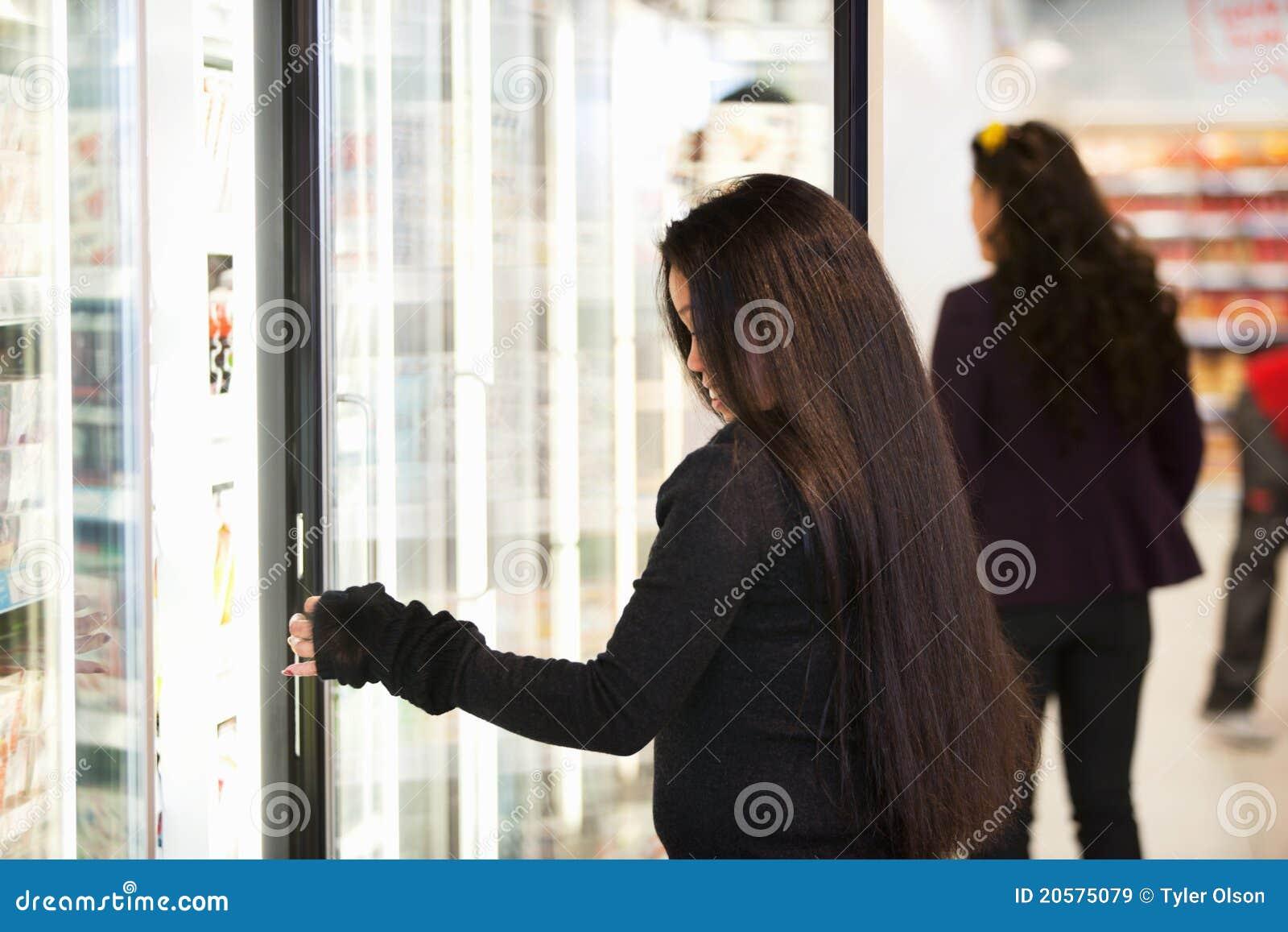 Junge Frau, die kalte Waren kauft