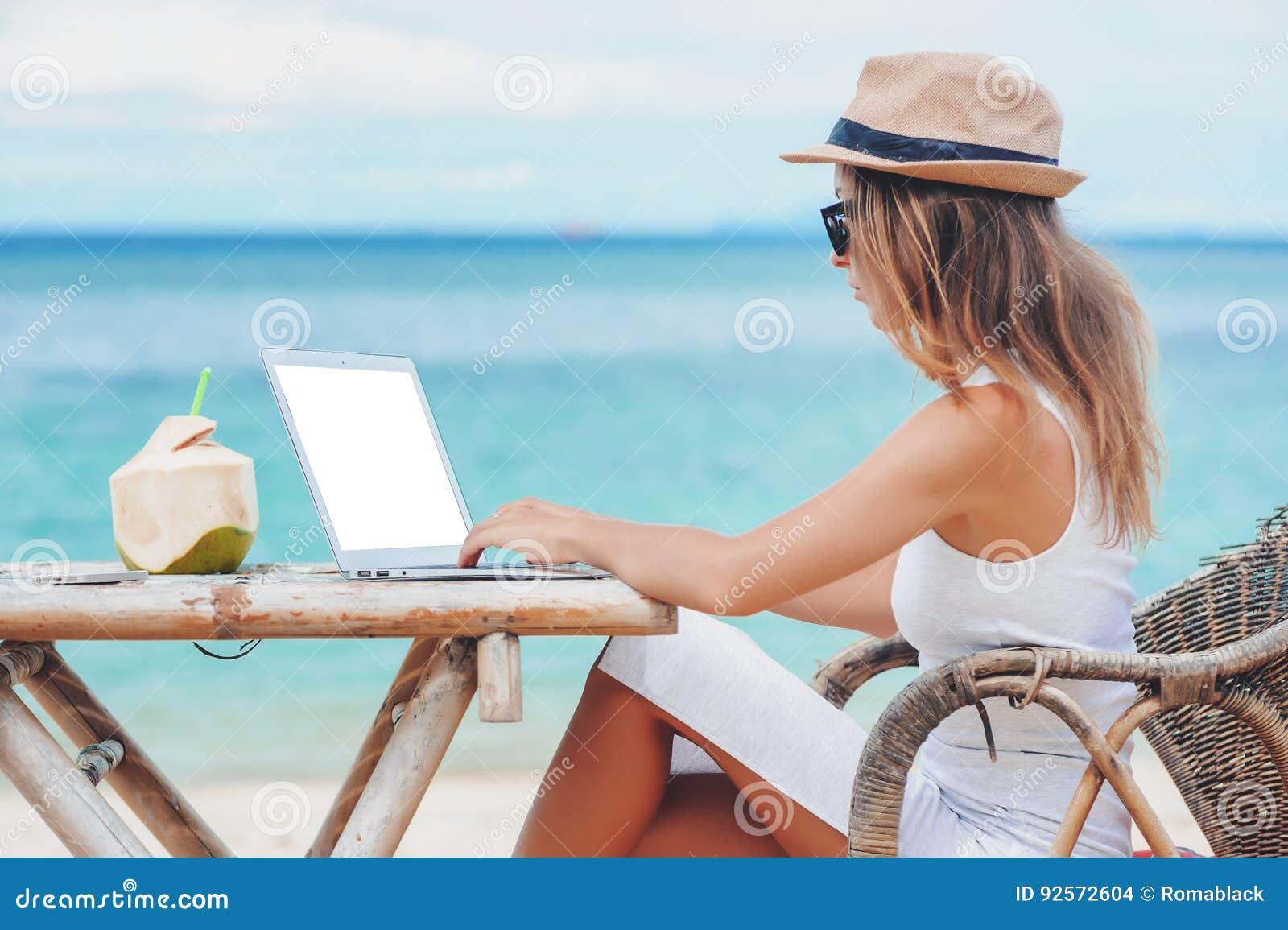 d53089b0069d Junge Frau, Die Laptop Auf Dem Strand Verwendet Freiberufliche ...