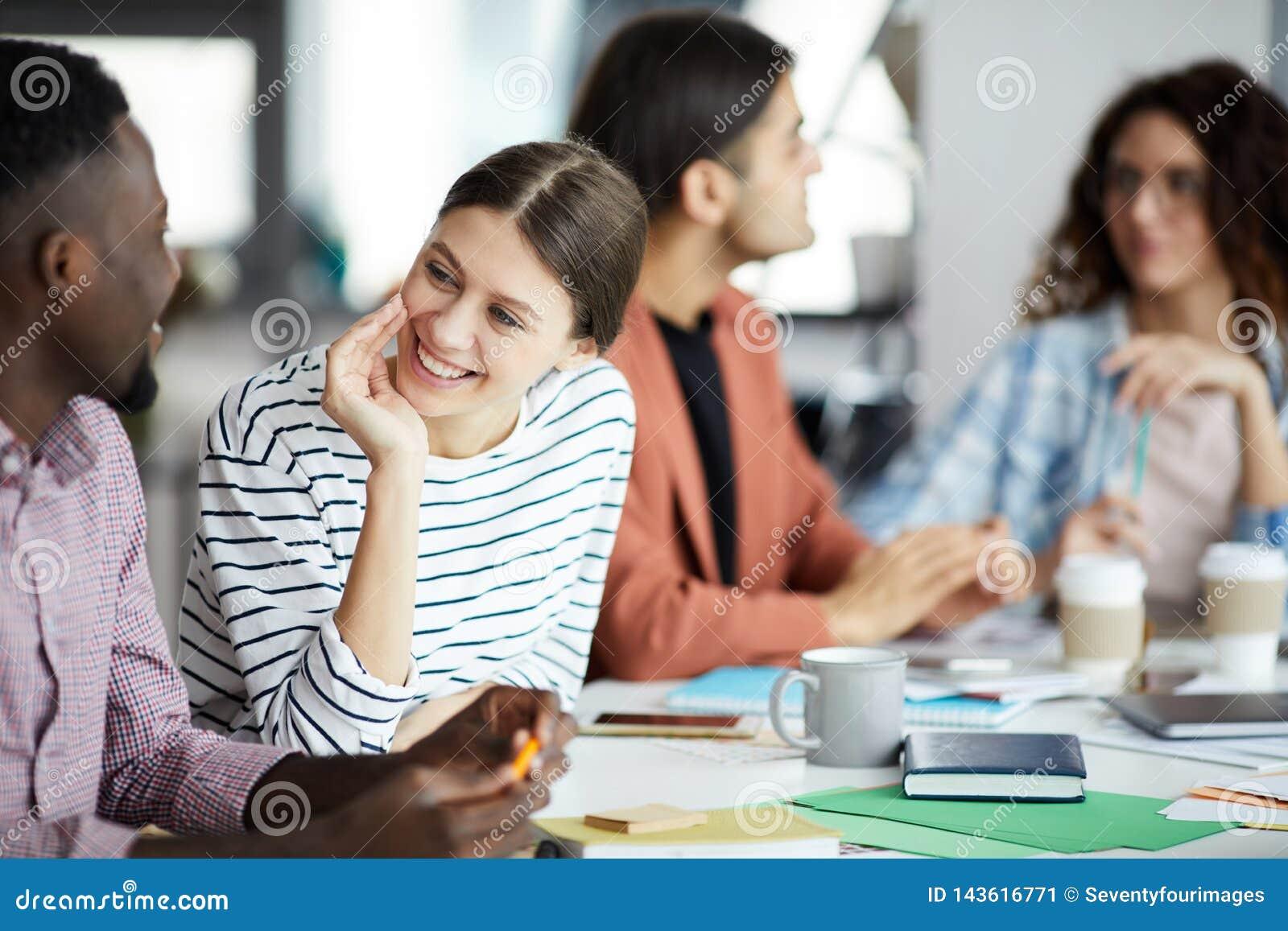 Junge Frau, die mit Kollegen in der Sitzung spricht