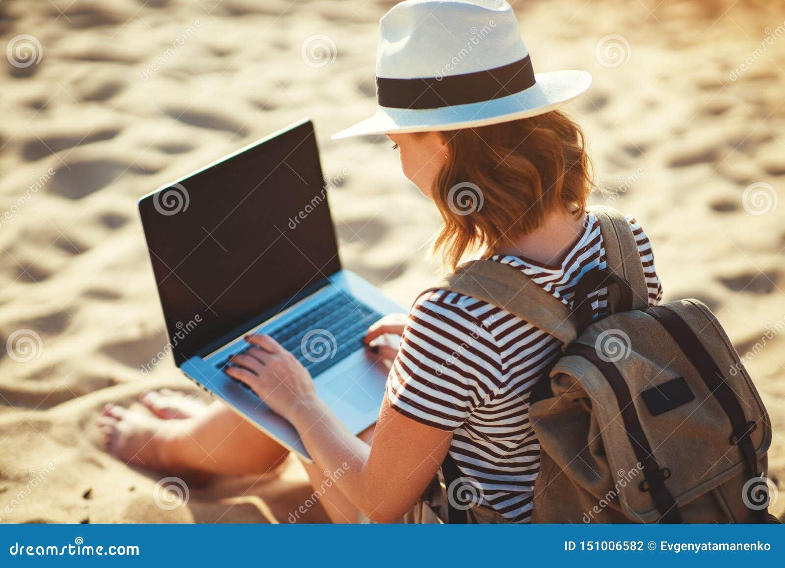Junge Frau, die mit Laptop auf Natur im Strand arbeitet