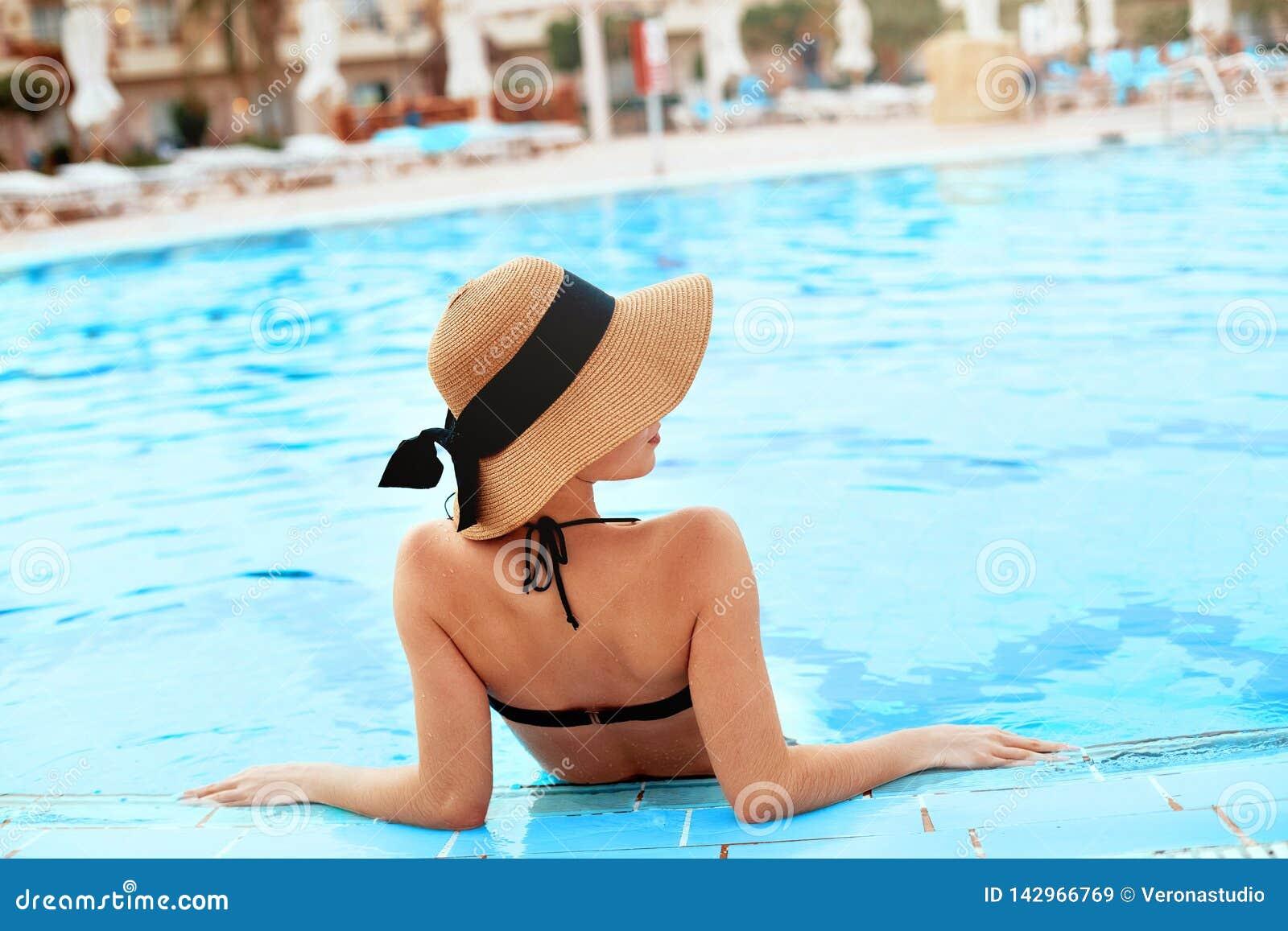 Junge Frau, die nahe dem Pool sitzt Sexy Mädchen mit gesunder gebräunter Haut Frau mit dem Sonnenhut, der im Swimmingpool sich