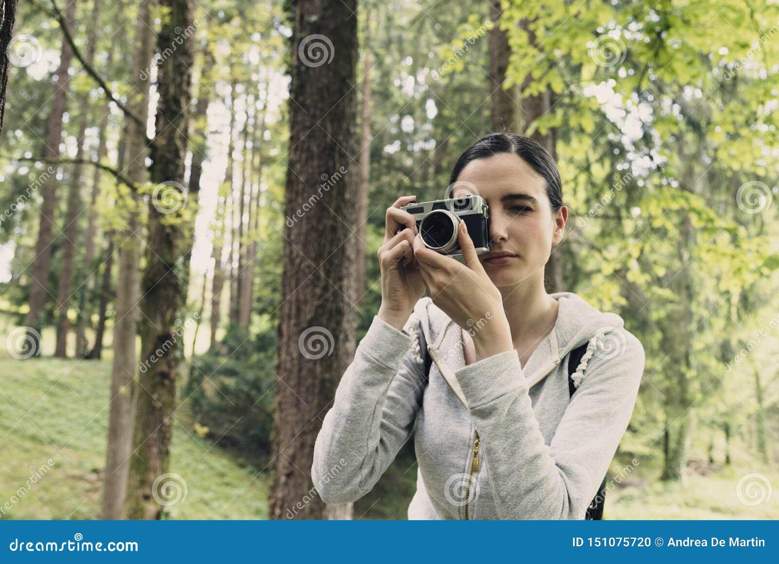 Junge Frau, die in Natur geht und Fotos macht