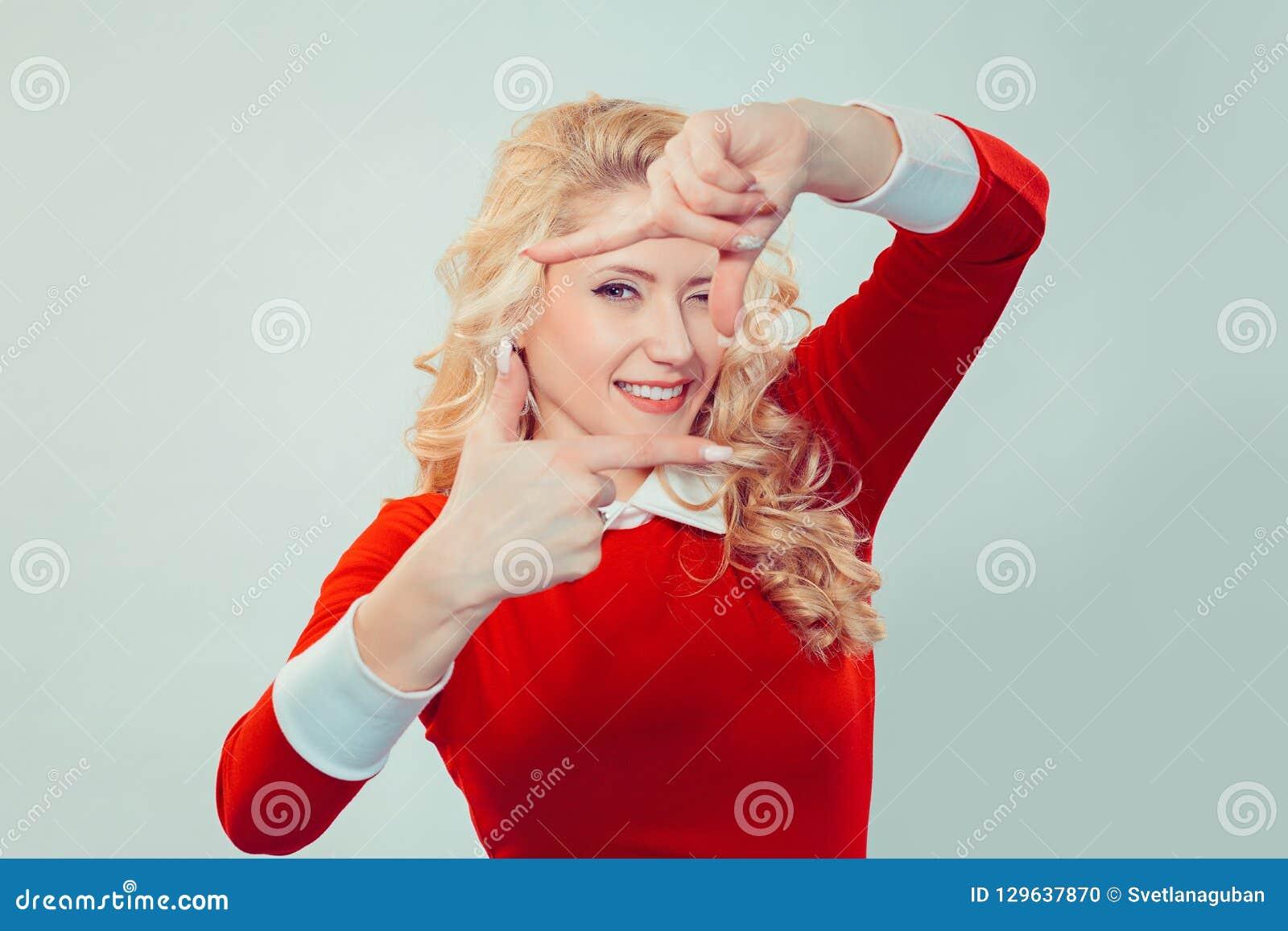 Junge Frau, die Rahmen mit den Händen betrachten Kamera macht