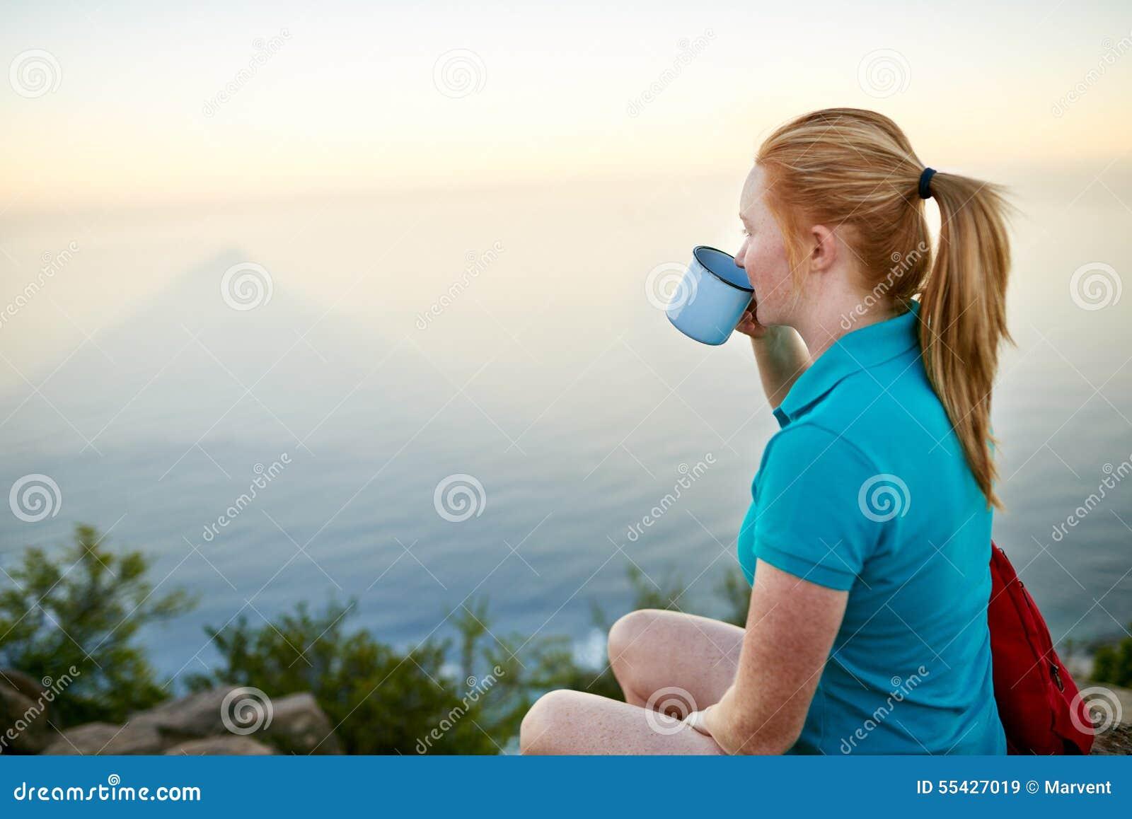 Junge Frau, die ruhig an ihrem Kaffee draußen nippt
