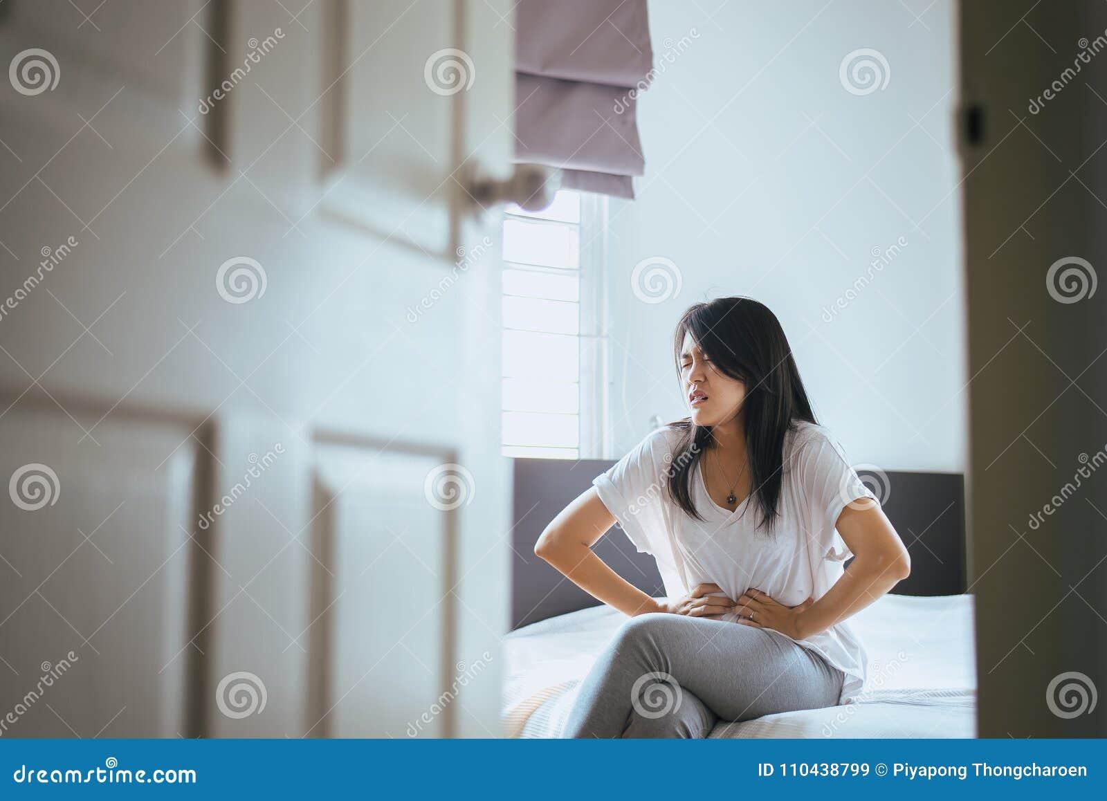 Junge Frau, die schmerzliche Magenschmerzen, weibliches Leiden von den Bauchschmerzen hat, während nach aufwachen Sie
