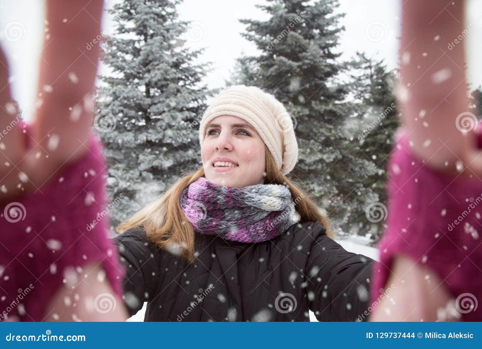Junge Frau, die selfie über Winterhintergrund nimmt Schneetag