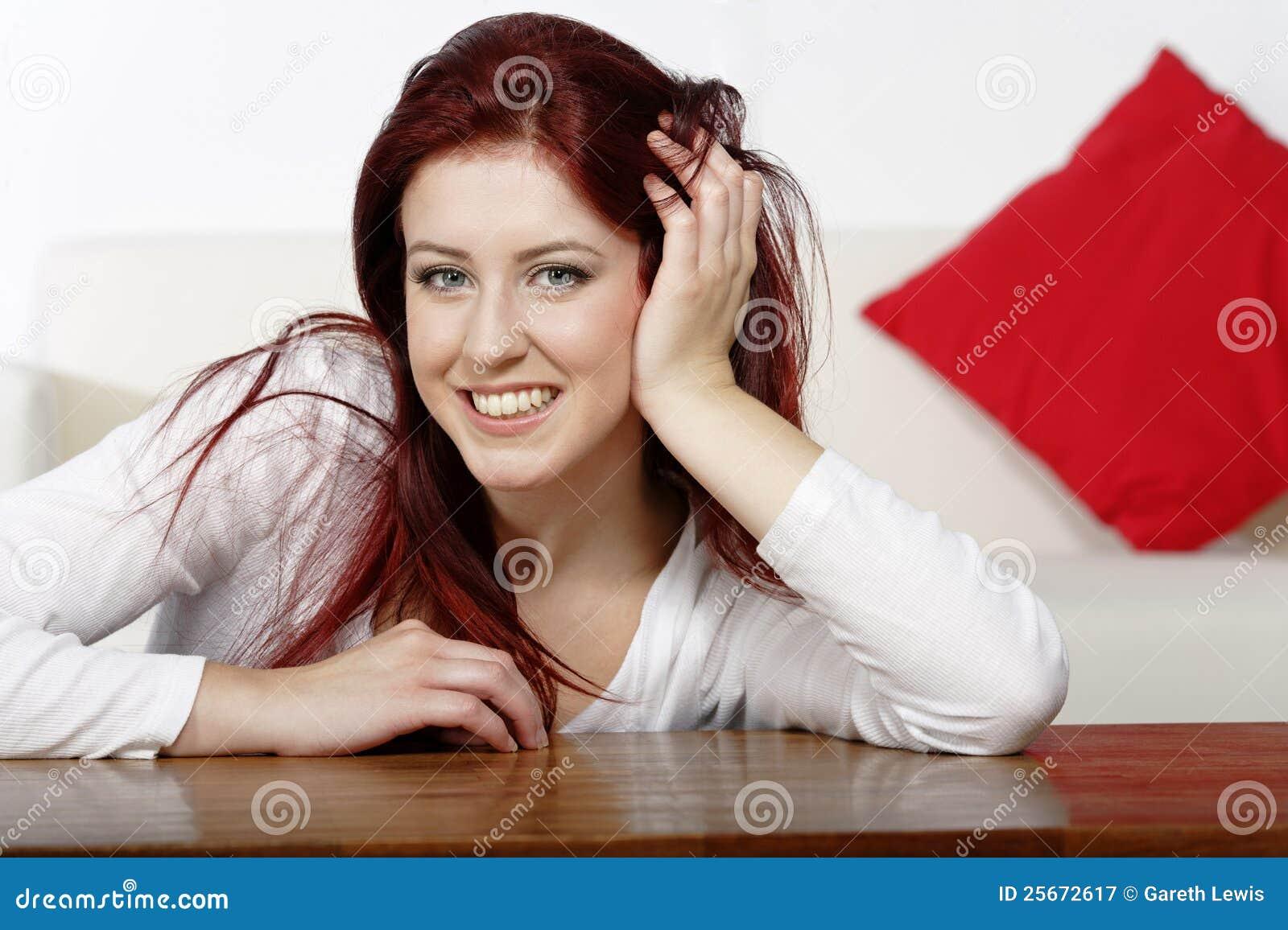 Schöne junge frau die zu hause auf einem kaffeetische vor sofa