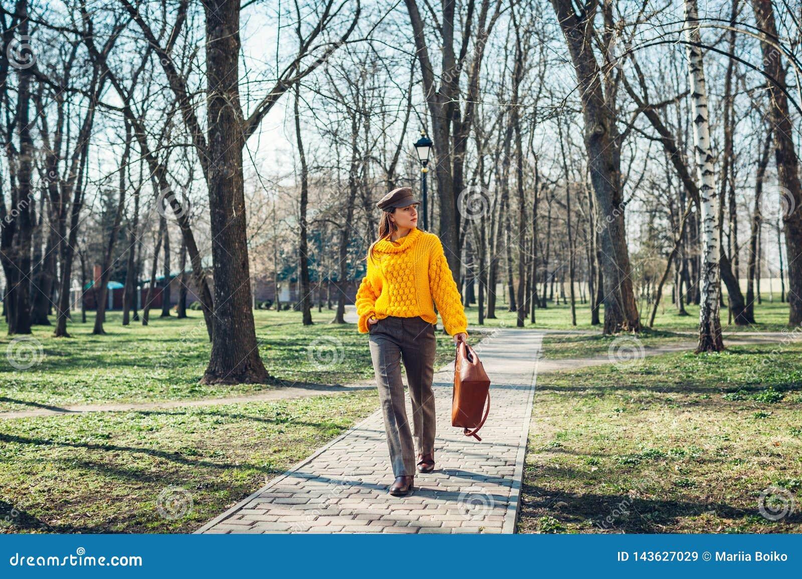 Junge Frau, die stilvolle Handtasche hält und gelbe Strickjacke trägt Frühlingsfrauenkleider und -zusätze Art und Weise