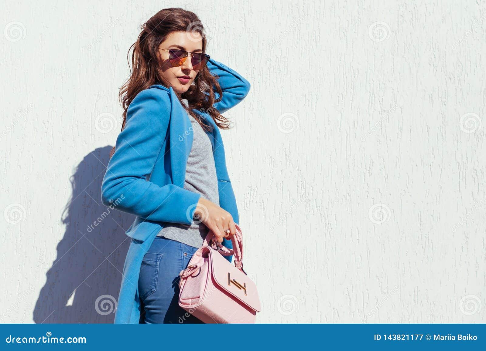Junge Frau, die stilvolle Handtasche h?lt und modischen blauen Mantel tr?gt Fr?hlingsfrauenkleider und -zus?tze Art und Weise
