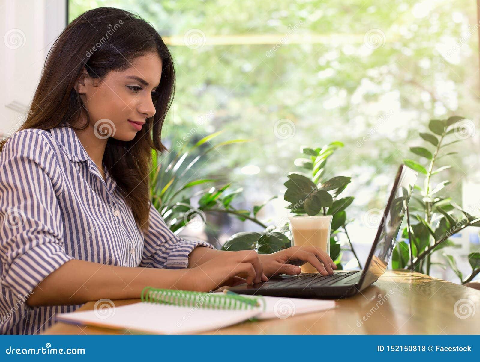 Junge Frau, die an trinkendem Kaffee des Caf?s stationiert und an Laptop arbeitet