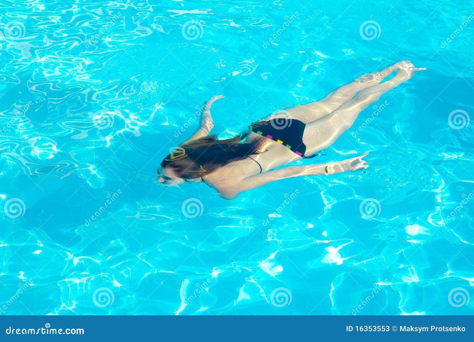 Junge Frau, die underwater im Pool schwimmt