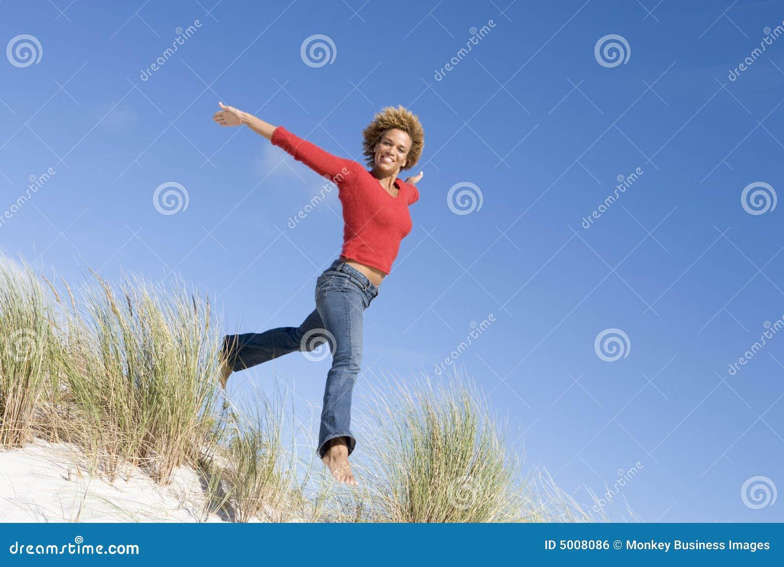 Junge Frau, die unter Sanddünen springt