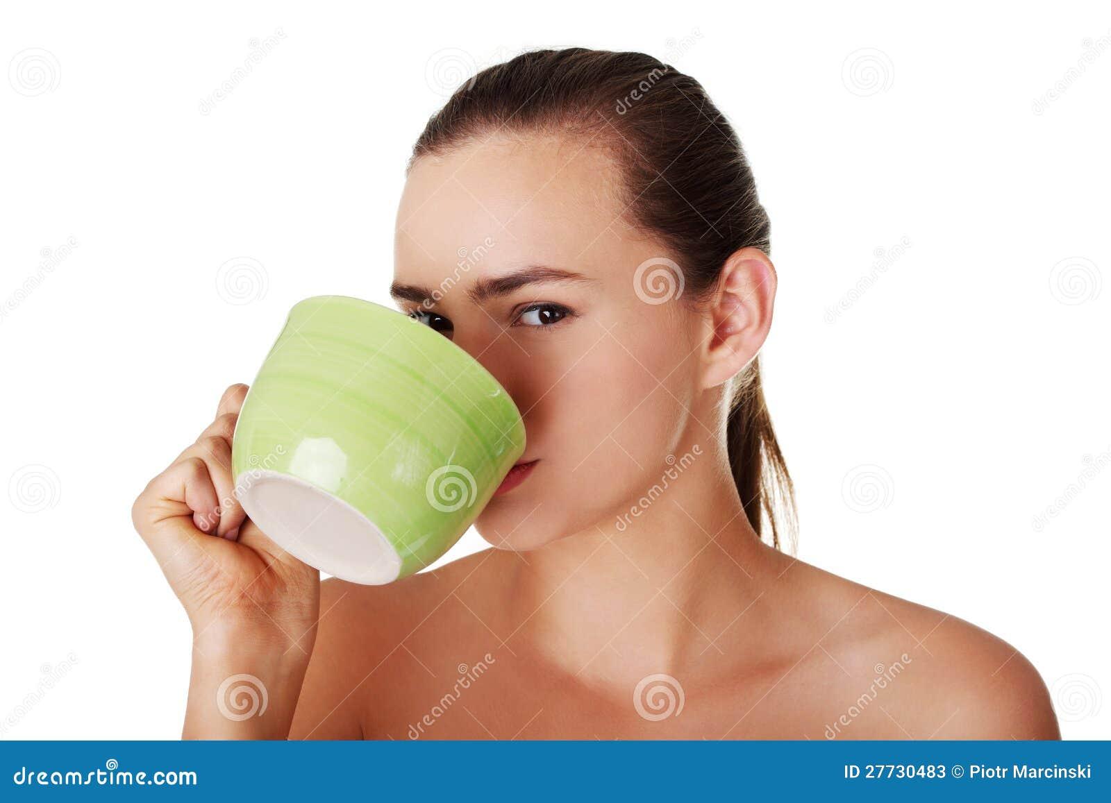 Junge Frau, die vom großen Becher trinkt