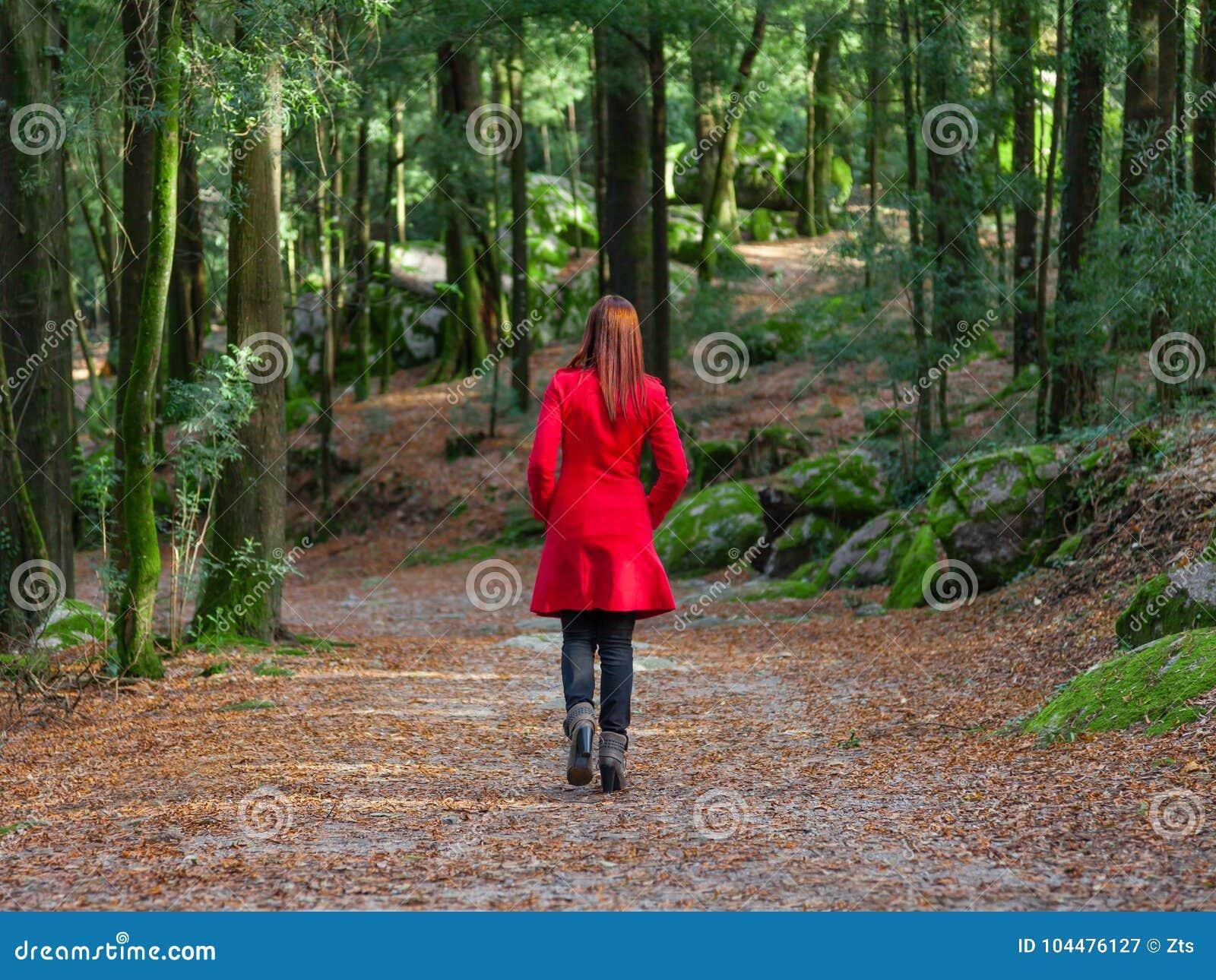 Junge Frau, die weg allein auf den Waldweg trägt roten langen Mantel geht