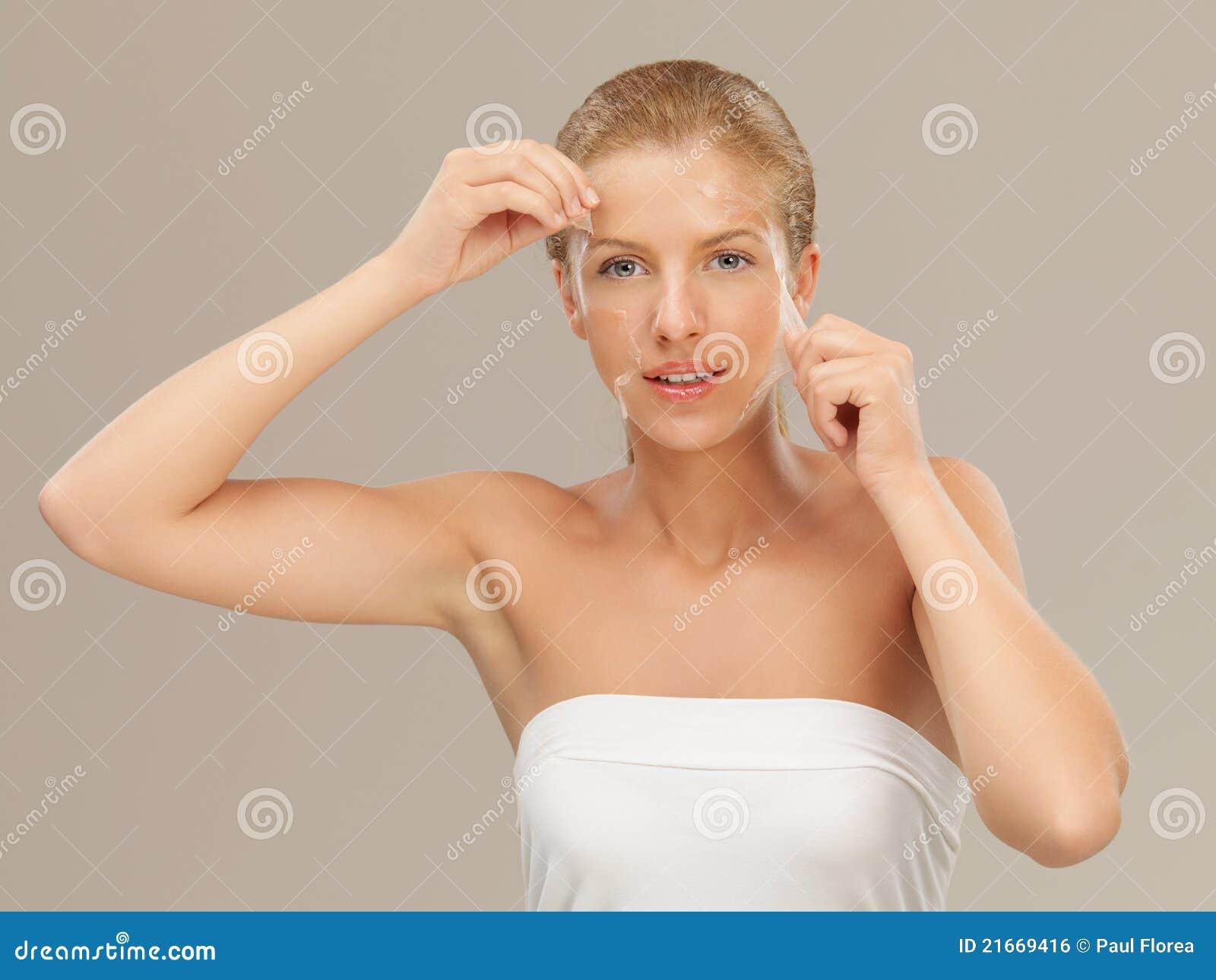 Junge Frau, die weg einem Gesichtsschablonenlächeln abzieht