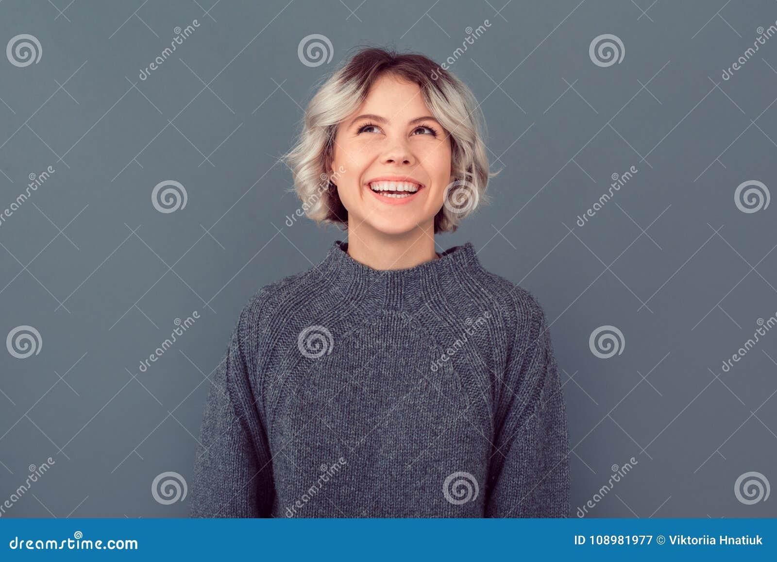 Junge Frau in einem grauen Strickjackenstudiobild lokalisiert auf dem grauen Hintergrund, der oben schaut