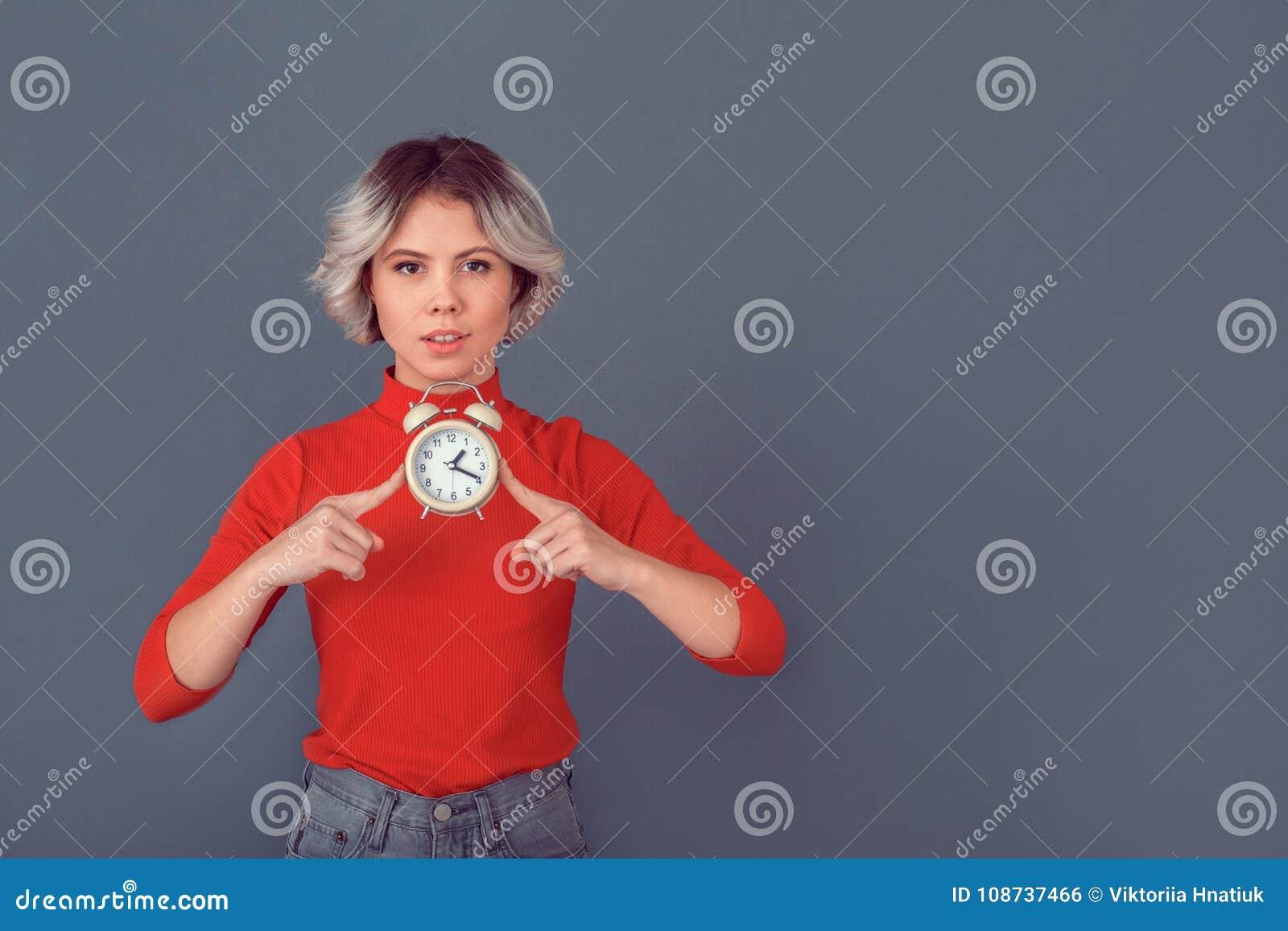 Junge Frau in einer roten Bluse auf grauer Wandzeit