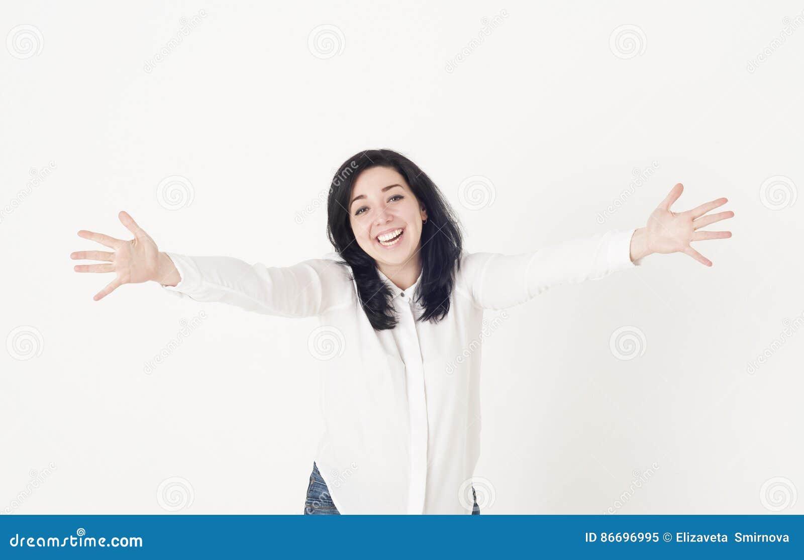 Junge Frau in einer weißen Bluse bereitet vor sich, jemand zu umarmen, verbreitet ihre Hände weit auseinander und grüßt das Läche