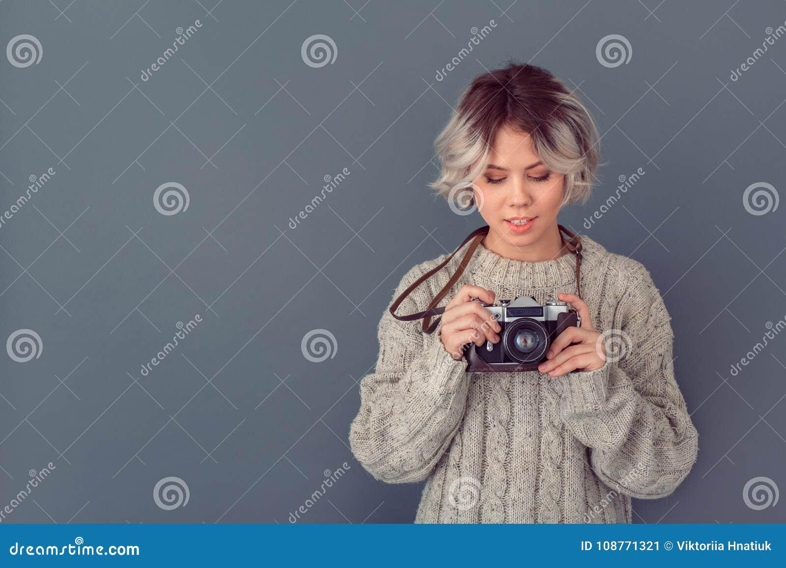 Junge Frau in einer woolen Strickjacke lokalisiert auf grauem Wandwinter-Konzeptan-/aus-schalter