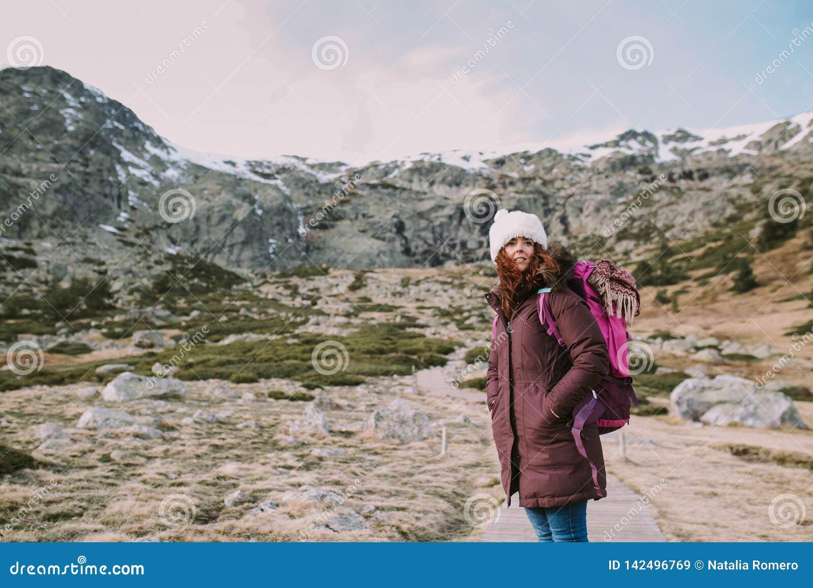 Junge Frau erwägt die schneebedeckten Berge