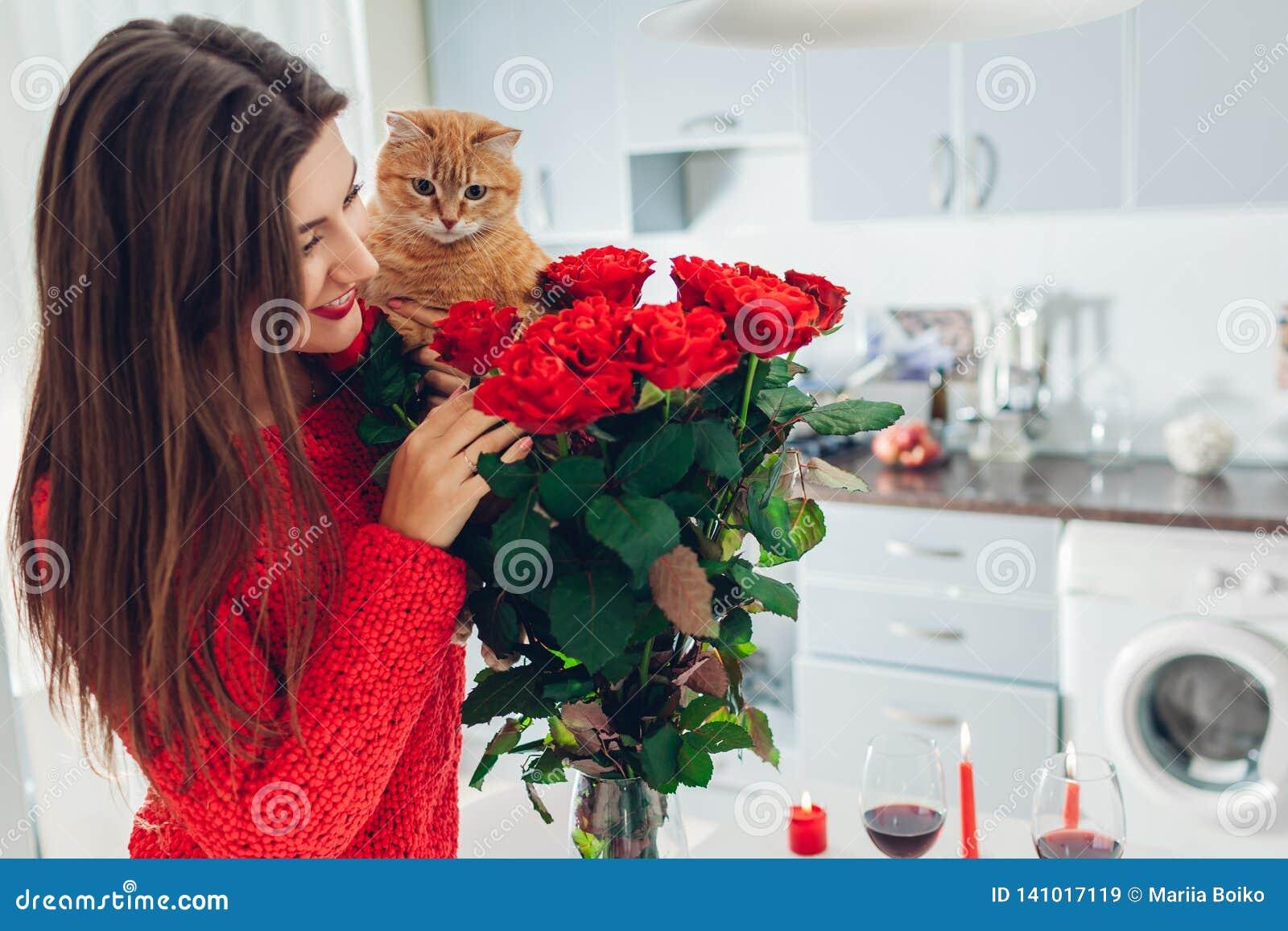 Junge Frau fand rote Rosen mit Kerze, Wein und Geschenkbox auf Küche Riechende Blumen des glücklichen Mädchens mit Katze