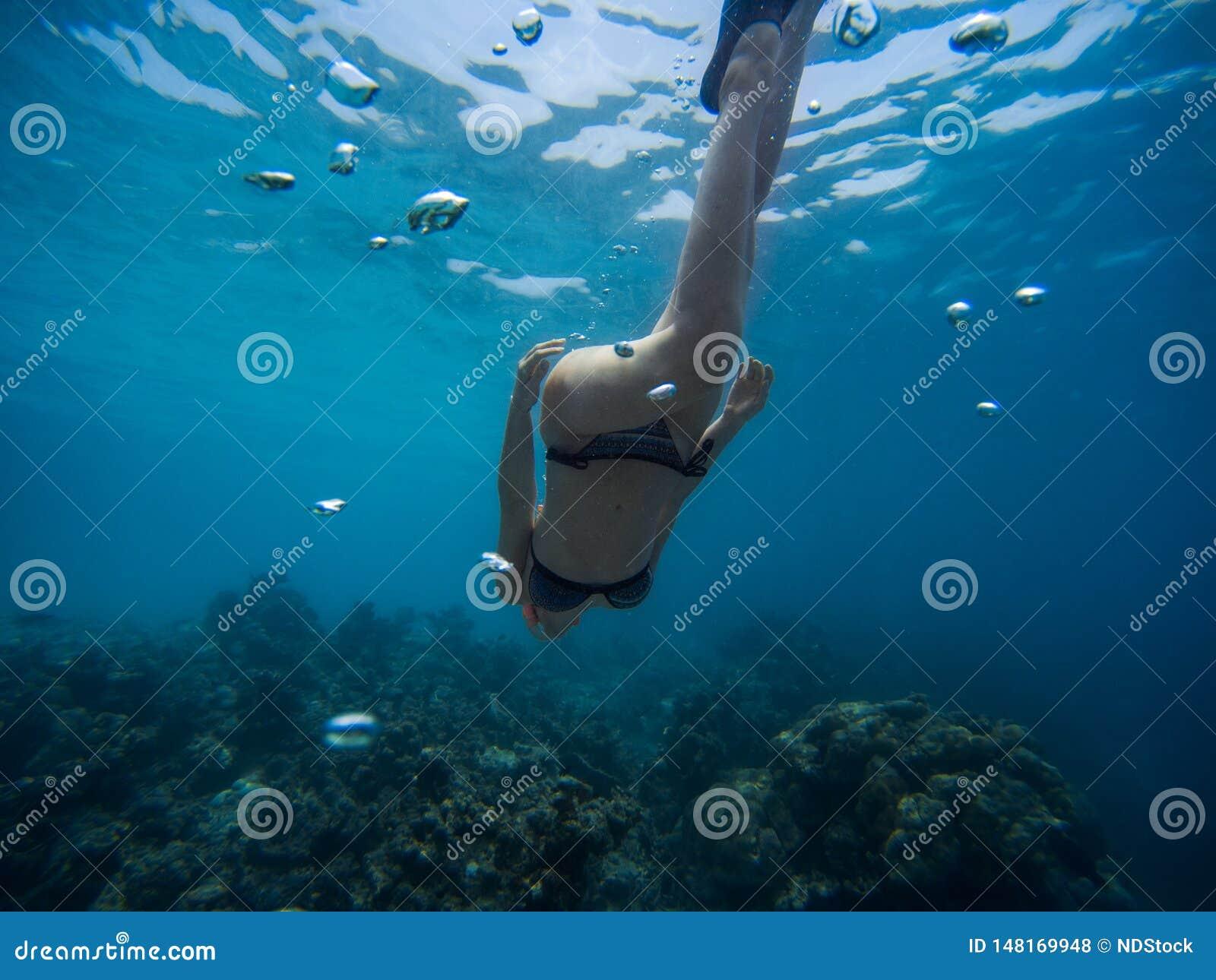 Junge Frau Freediver schwimmt unter Wasser mit Schnorchel und Flippern